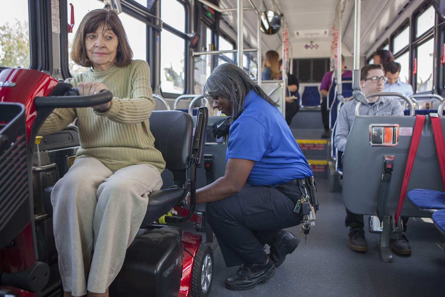 woman on mobility scooter getting buckled in by bus driver