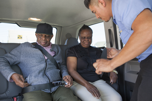 paratransit driver buckling in african american couple