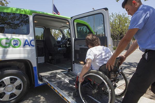 paratransit driver pushing person in wheelchair up ramp into van