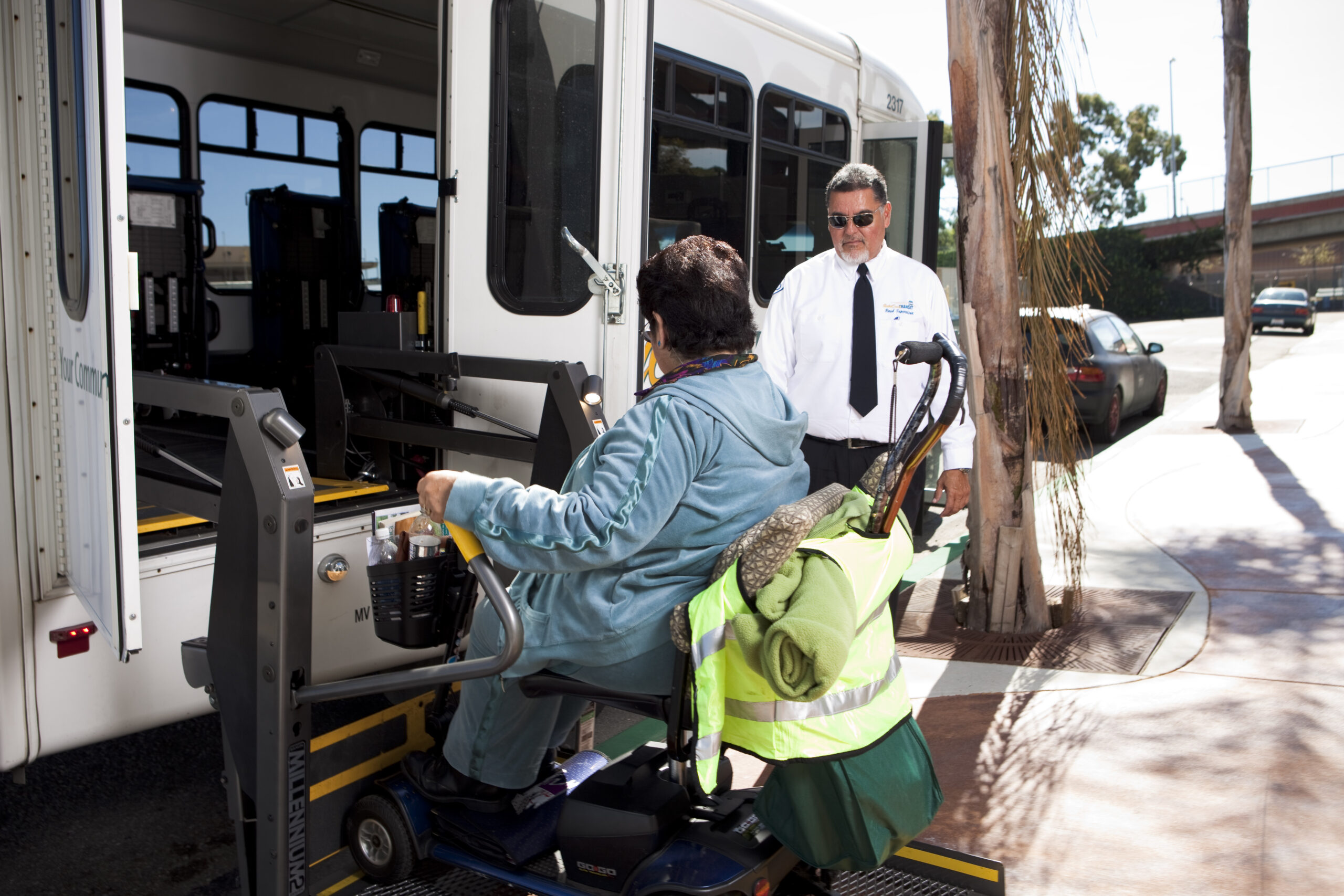 man in wheelchair using chair lift to get on the bus