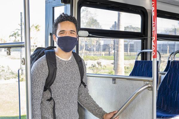 man wearing mask entering the bus