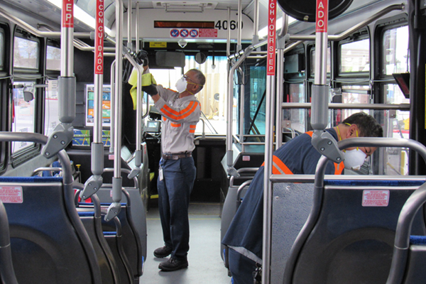 2 workers sanitizing the inside of a bus