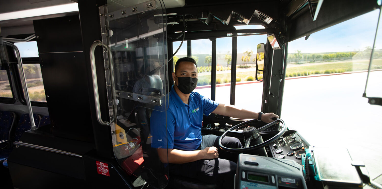 Bus driver with mask in drivers seat